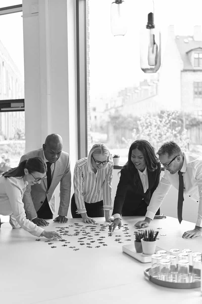 Group of corporate professionals solving a puzzle at the table