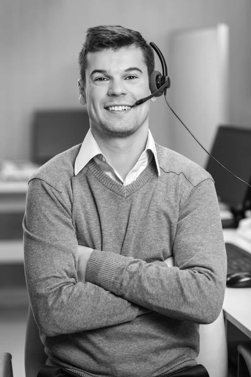 Smiling customer support representative man wearing a headphone at his workplace