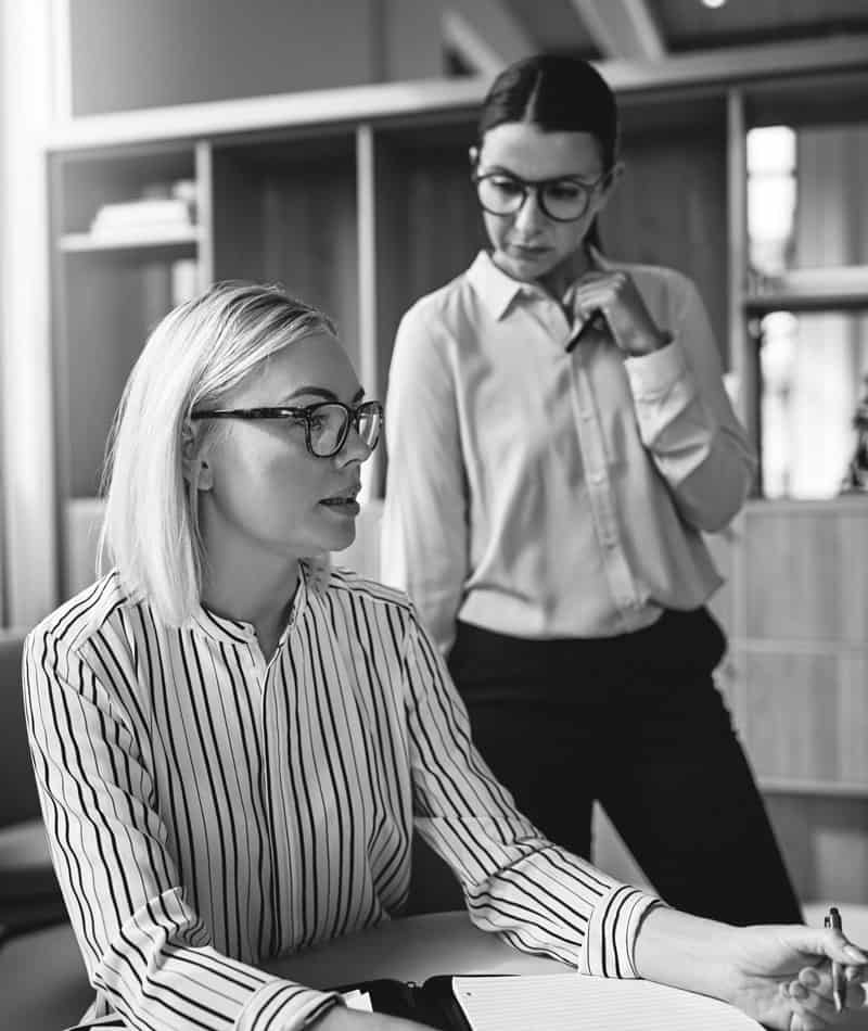 Businesswoman wearing spectacle explaining with her lady assistant standing next to her