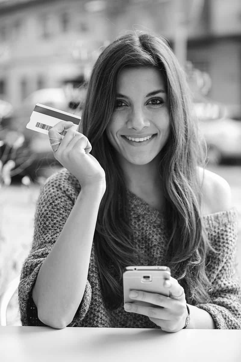 Smiling woman doing an online payment with credit from her phone
