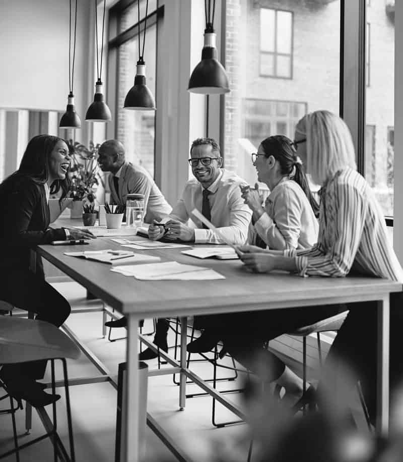 Team of business professionals smiling and having a casual chat at the table