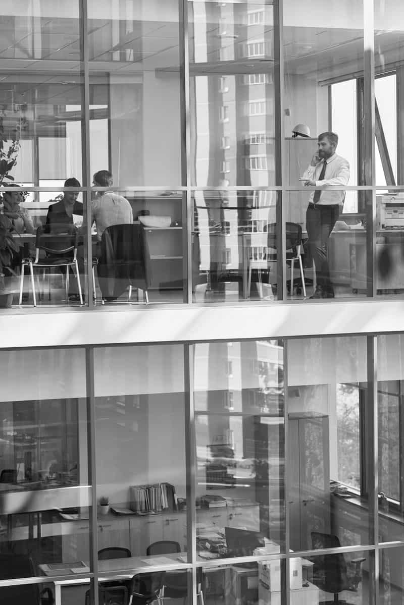 Businessman standing in front of panoramic window and having a phone call with people sitting behind.
