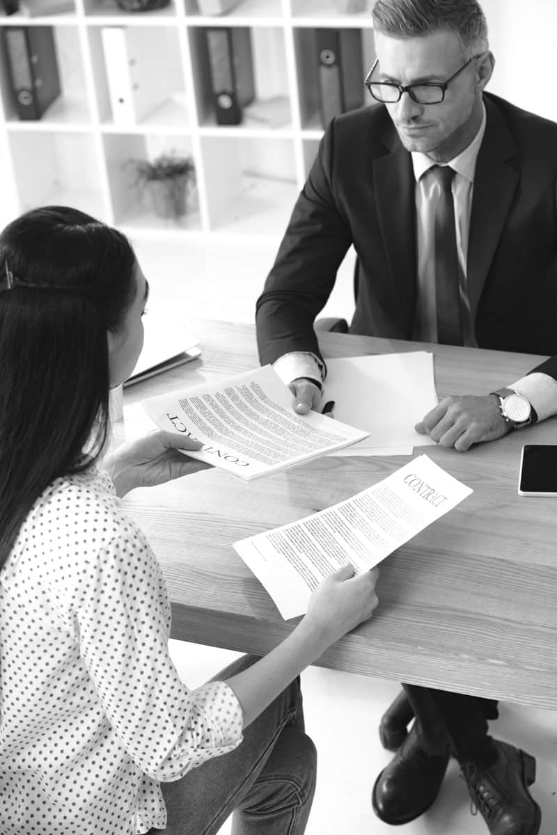Businessman giving contract papers to the lady sitting at the desk